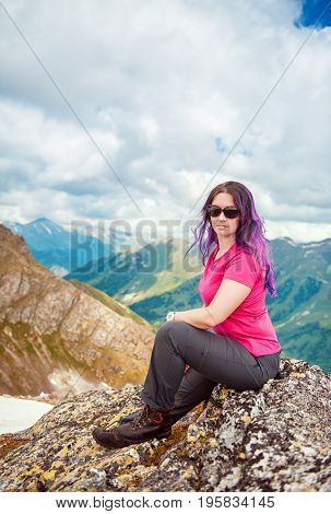 Woman hiker sitting on the top of mountain outdoor
