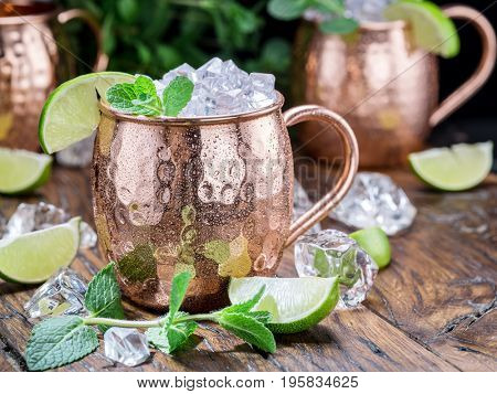 Moscow Mule. Frosty copper mug with lime and ice cubes on the wooden table.