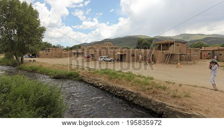 TAOS, NEW MEXICO, JULY 5. The Taos Pueblo on July 5, 2017, near Taos, New Mexico. A Woman Tourist Photographs Red Willow Creek from South House in the Taos Pueblo near Taos in New Mexico.