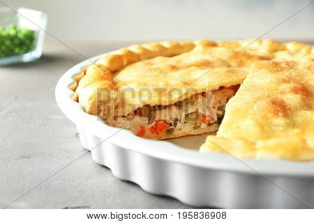 Baking dish with turkey pot pie on light gray background