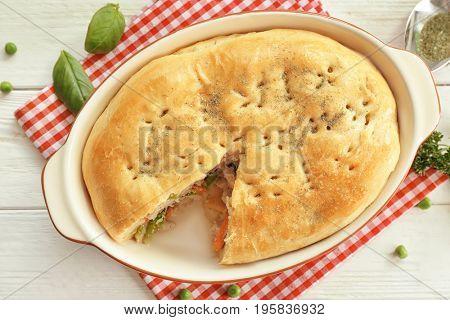 Baking dish with turkey pot pie on white wooden background, closeup