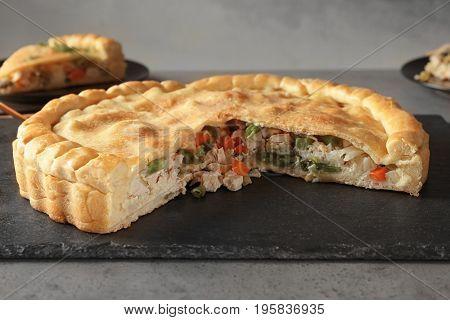 Slate plate with tasty turkey pot pie on gray table
