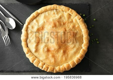 Slate plate with delicious turkey pot pie on gray table