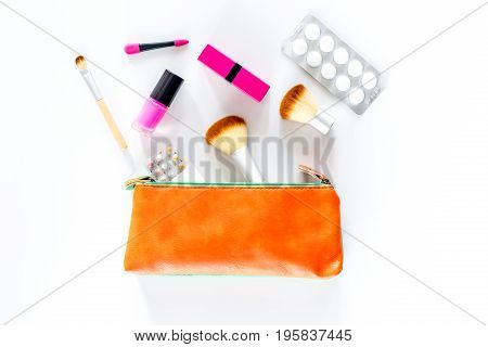 Beauty bag with cosmetics, contraceptives and pills on white table background top view.