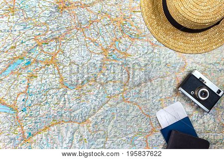 Map of roads with a vintage camera, passport, sunglasses. View from above. The concept of travel. Copy space. Flat lay