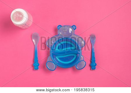 Baby bottle and blue plate with spoon and fork isolated on pink. Top view. Copy space. Flat lay
