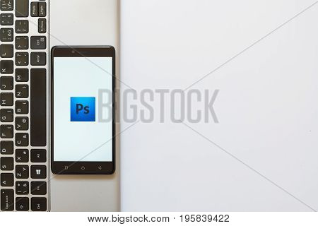 Los Angeles, USA, july 18, 2017: Adobe photoshop logo on smartphone screen placed on the laptop on white background.