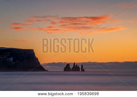 Reynisdrangar rock formation and Reynisfjara cliff in sunrise Iceland