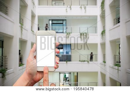 female hand holding mobile smart phone touch screen showing white screen for insert text and picture over the inside the building with many floors is blur background