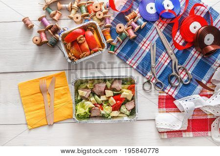 Lunch box healthy food delivery for dressmaker top view. Flat lay shot of foil container with diet meal for fashion designer at workplace. Diet nutrition, meat and vegetables