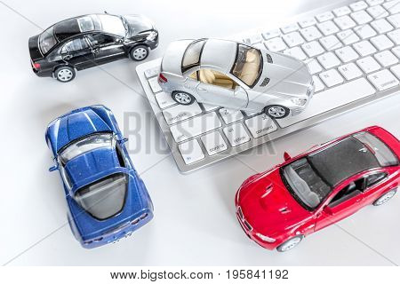 Choosing car online. Toy cars on keyboard white background top view.