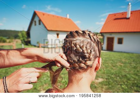 Young woman making hair braids of the little girl on the garden in the countryside.