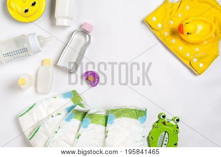 Babies goods diaper, baby powder, cream, shampoo, oil on white background with copy space. Top view or flat lay. Maternity concept