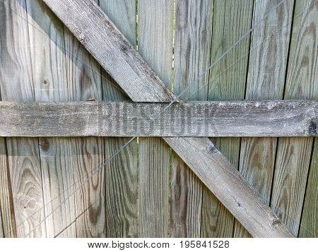 wood fence with brown wood boards criss crossing each other