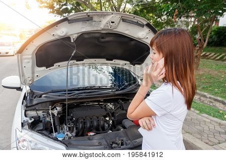 Stressed woman calling for help on cell phone with mobile phone - car breakdown