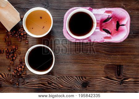 Coffee take away. Coffee cups with covers and coffee beans on wooden table backound top view.