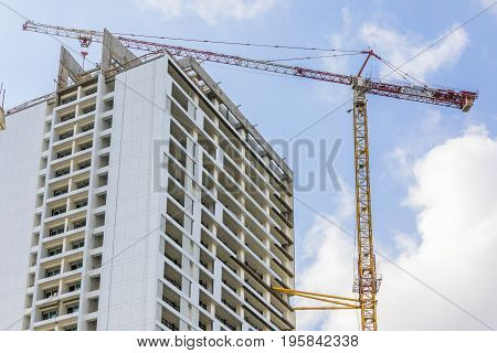 Tower crane jib above multistory building under construction with blue sky and clouds