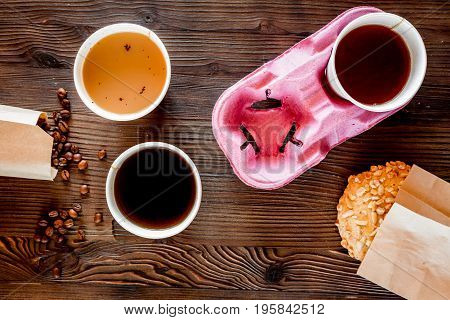 Coffee take out. Coffee cups with covers, coffee beans and cookies on wooden table backound top view.