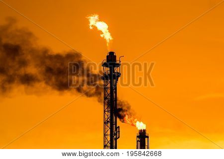Chimney with fire and orange sky background