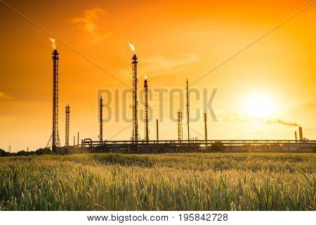 Refinery factory silhouette at orange summer sunset