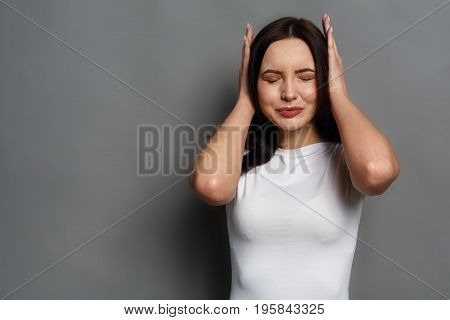 Confused woman puts her hands on the head. Portrait of young sad girl closing her ears, hear nothing, deafness concept