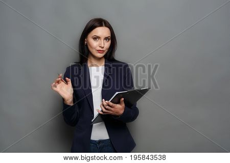 Confident elegant business woman in formal suit standing with notepad on gray studio background, looking at camera, copy space