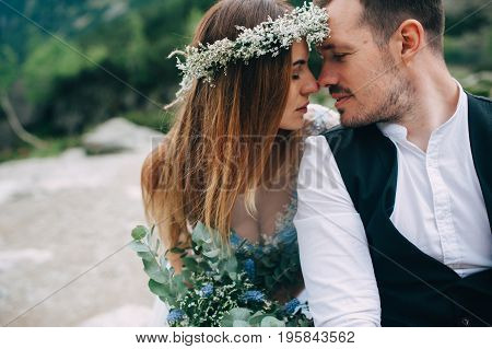 bride with a beautiful wreath of white flowers and the groom standing face to face