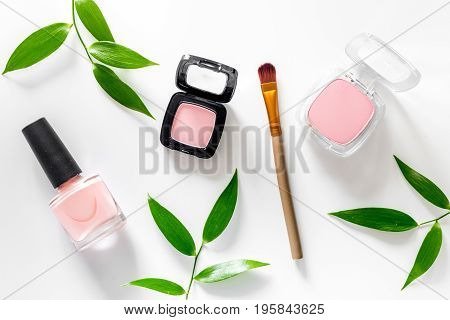 Cosmetics. Eyeshadow, blush and nail polish on white table background top view.