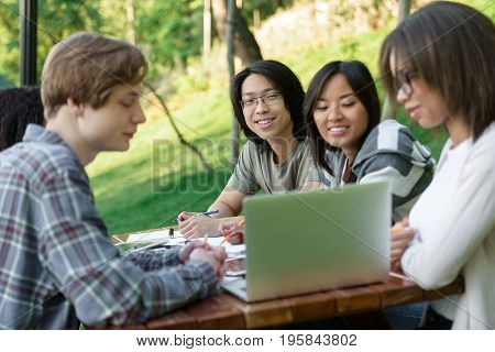 Image of multiethnic group of happy young students sitting and studying outdoors while using laptop. Looking aside.