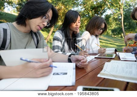 Multiethnic group of concentrated young people sitting and studying outdoors. Looking aside.