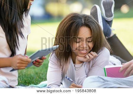 Photo of multiethnic group of cheerful young students sitting studying outdoors. Looking aside.