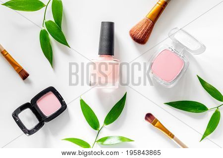 Cosmetics. Eyeshadow, blush, brushes and nail polish on white table background top view.