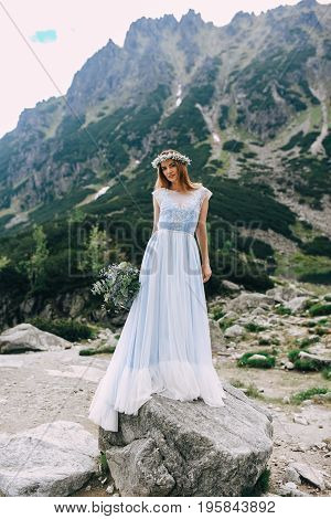 the bride in a beautiful blue dress and a wreath of white flowers holding a bouquet of purple flowers and eucalyptus overlooking the green mountains