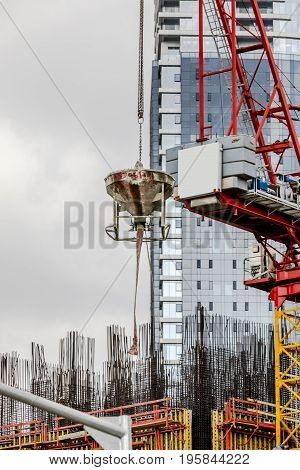 Construction tower crane moving concrete bucket on construction site with corporate building on background vertical