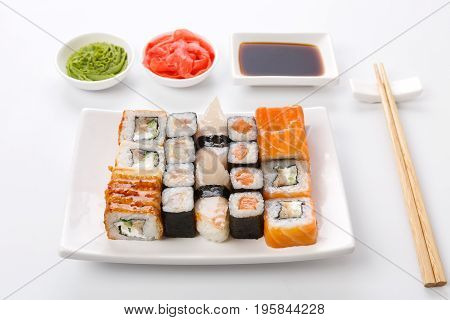 Traditional japanese food delivery. Sushi set on white plate, soy sauce, ginger, wasabi and chopsticks aside. Colorful rolls and gunkan assortment at white background, pov
