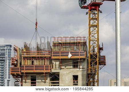 Construction worker wearing yellow hard hat and safety vest secure the crane chain on scaffold with residential building on background