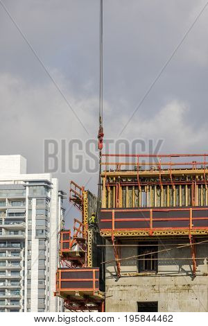 Construction worker wearing yellow hard hat and safety vest on side of scaffold with residential building on background vertical