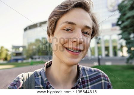 Image of happy student man standing outdoors. Looking at camera.