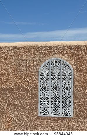 Arabic style window on a wall and the sky behind