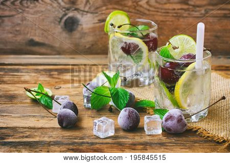 Two glasses with drink with straw frozen cherries lemon lime and mint leaves ice cubes on napkin on wooden table