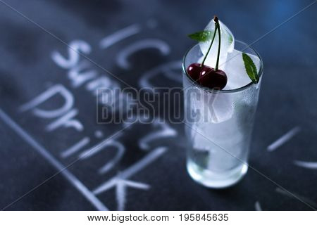 Natural ice in a glass with cherries on a black background