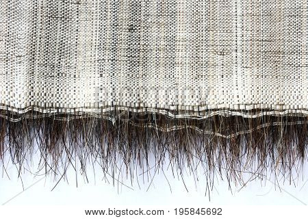 Old rough textural fabric with horsehair abstract textile background edge on white