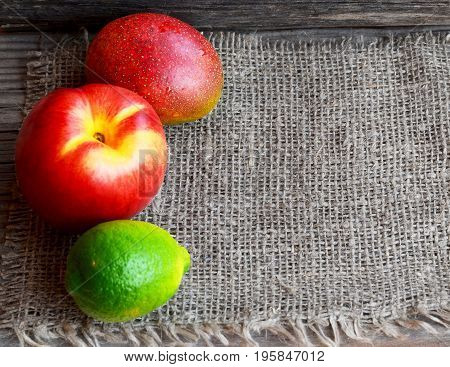 Fresh ripe organic peach,lime and mango on burlap cloth background.Tropical fruits.Diet,healthy food,raw food concept.