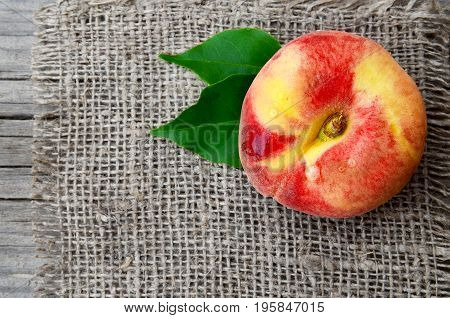 Chinese flat peach with leaves on burlap napkin.Donut peache also known as Paraguayo peach.Healthy food or Diet concept.