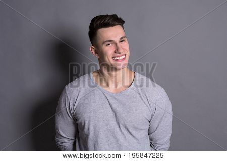Handsome positive young man isolated on gray studio background