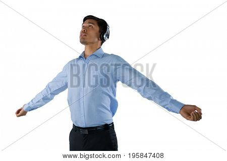 Businessman listening music while standing with arms outstretched against white background