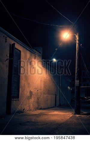 Dark urban city downtown alley at night with moon, large street light and cars.