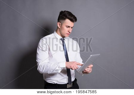 Successful businessman. Young man working on digital tablet at gray studio background.