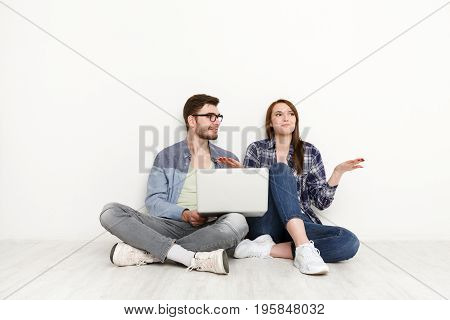 Couple discuss something, sitting on floor with laptop on white background at new apartment