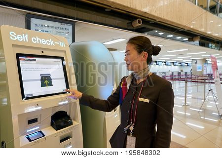 SEOUL, SOUTH KOREA - CIRCA MAY, 2017: female staff at Gimpo Airport International Terminal self-service check-in area. Gimpo International Airport is located in the far western end of Seoul.